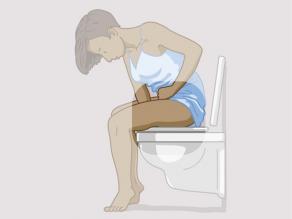 Femme assise sur les toilettes et tenant un bras entre les jambes. L'attention porte sur le bras entre les jambes.